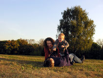 Family plays autumn on sundown on glade. Tree royalty free stock images