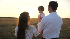 The family plays with the baby at sunset. Dad and Mom walk with her daughter in her arms at sunset. father with stock footage