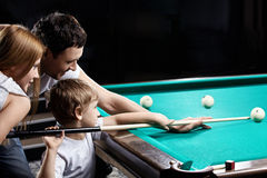 The family plays billiards. The young couple and the child plays billiards Royalty Free Stock Photos