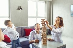 The family plays board games inside the room. The family plays board games gaily while sitting at the table inside the room Stock Photography