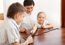 Family that plays dominoes. Father playing with children at home Royalty Free Stock Images