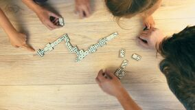 The family plays dominoes on the table. View from above.