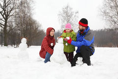 Family plays in park in winter. Family from three persons plays in park in winter and sculp snowman Royalty Free Stock Images
