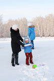 Family plays in the snow Stock Photos
