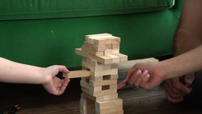 The family plays wooden tower. The close-knit family collects from small wooden blocks a tower on the toy railroad. The. On this video you can see as the young stock footage