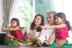 Family pointing away. Happy Indian family at home. Asian people laughing and pointing to somewhere. Parents and children indoor lifestyle Royalty Free Stock Photos