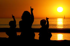 Family Pointing At The Sun. Family looking at a late sunset on the beach, all pointing at the sun Stock Photo