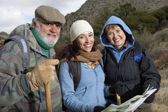 Family With Poles And Map Hiking Together In Desert Stock Photos