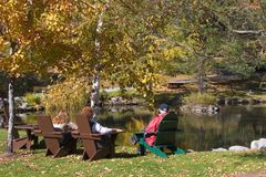 Family by Pond. Family Sitting by a Pond in Autumn Stock Images
