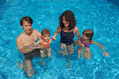 Family in the pool. Happy family of four having fun in the pool Royalty Free Stock Photography