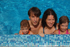 Family in the pool. Happy family of four having fun in the pool Royalty Free Stock Photo