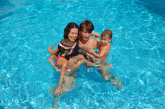 Family in the pool. Family of four having fun in the pool Stock Image