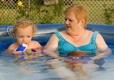 Family in Pool. Young boy and woman sitting in swimming pool Stock Image