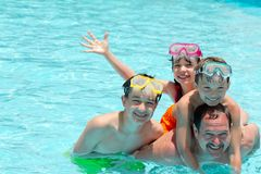 Family in pool. Smiling father and three children with goggles in a pool Stock Image