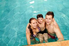 Family in pool. Photo of happy family of three in swimming pool smiling at camera Stock Photos