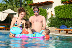 Family in pool. Man, women and children in pool royalty free stock image