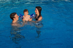 Family pool fun. Family with a child in swimming pool Stock Image