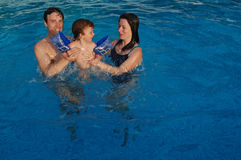 Family pool fun. Family with a child in swimming pool Royalty Free Stock Image