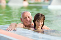 Family in the pool. Grandfather with granddaughter enjoying in the swimming pool Royalty Free Stock Photography