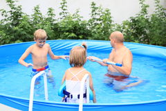 Family in pool. Happy family in a pool - little girl with swimming belt on stairs, boy freezing in the water and kneeing men cleaning the pool Royalty Free Stock Images