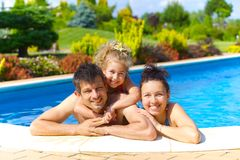 Family in the pool. Pretty little girl with her parent in swimming pool outdoors Royalty Free Stock Photos