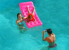 Family in pool take pictures Royalty Free Stock Photography