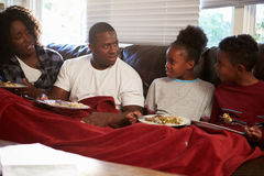 Family With Poor Diet Sitting On Sofa Eating Meal. Whilst Trying To Keep Warm Under Red Blanket stock image