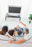 Family with popcorn watching their television on sofa Stock Photography