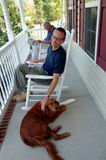 Family on the Porch. A man, his father and pet dog sitting on the front porch of their house Stock Photography