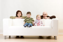 Family Portrait. A portrait of a cute family, on a sofa royalty free stock photo