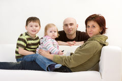 Family Portrait. A portrait of a family sitting on a sofa stock images