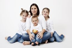 Family portrait. Portrait of mother, son and twin girls in a studio Stock Images