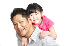 Family portrait of Asian Chinese father, daughter. Family portrait of young Chinese father piggybacking little daughter dressed in pink. Shot in studio, isolated Stock Photography