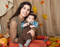 Family portrait in autumn season. Woman and little boy sit on yellow fall leaves, apples, pumpkin and decoration Stock Photos