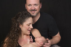 Family portrait with baby. Portrait of a family with mother, father and tiny baby Stock Image