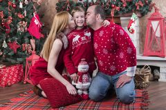 Family portrait at the Christmas tree. Mother and father kissing son sitting on the floor near the Christmas tree stock photography