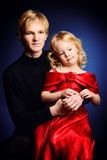 Family portrait. Portrait of an elder brother and his little sister over black background stock photography