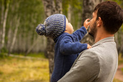 Family portrait. Father play with his child. Father holding a child in his arms. They are happy. Happy family walking outdoor. Photo Royalty Free Stock Image