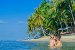 Family portrait: father and son sitting in the water on a tropic royalty free stock images