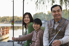 Family portrait with fishing gear at a lake royalty free stock images