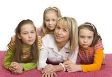 Family portrait on the floor. Family portrait. There're 3 girls and their mother lying on the pink carpet. They're looking at camera Royalty Free Stock Images