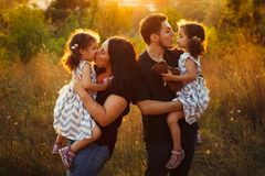 Family portrait of four in autumn forest park with little girls twins. Happy people, smiling and kissing. Warm evening sunlight. Family portrait of four in Stock Image