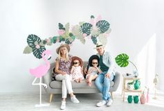 Family portrait of four. Happy parents in big hats and thier cheerful kids. Small girl and boy in black glasses, sitting at the sofa at home, all smiling stock images