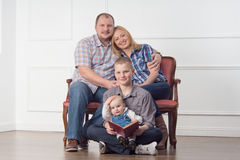Family portrait. Full length family portrait with parents and two children sitting on sofa and reading a book, studio shot Stock Photo