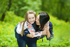 Family portrait of a girl and mother in the park on a background Stock Photography