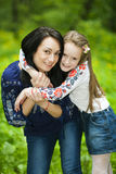 Family portrait of a girl and mother in the park on a background Royalty Free Stock Image