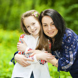 Family portrait of a girl and mother in the park on a background Royalty Free Stock Images