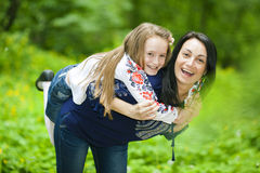 Family portrait of a girl and mother in the park on a background Stock Images
