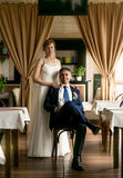 Family portrait of groom sitting on chair and bride standing beh Royalty Free Stock Image
