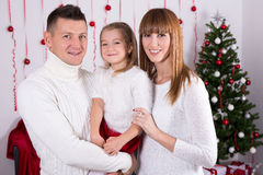 Family portrait of happy parents and daughter with Christmas tre Stock Photos